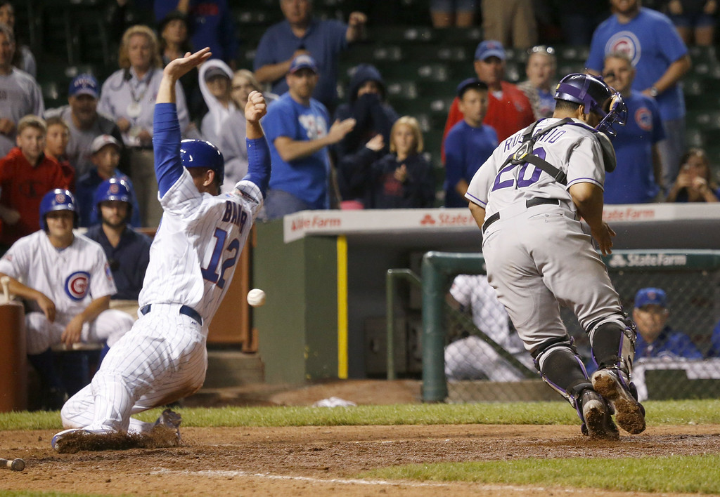 . Chicago Cubs\' John Baker, left, scores the game winning run off a sacrifice fly by Starlin Castro, as the ball gets past Colorado Rockies catcher Wilin Rosario (20) during the 16th inning of a baseball game Tuesday, July 29, 2014, in Chicago. The Cubs\' won 4-3. (AP Photo/Charles Rex Arbogast)