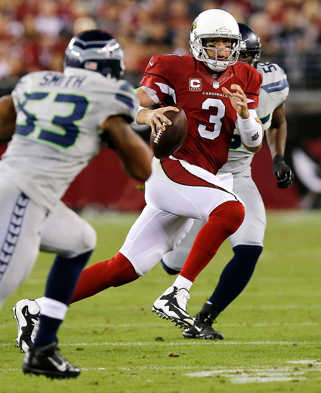 . Arizona Cardinals quarterback Carson Palmer (3) scrambles under pressure from Seattle Seahawks outside linebacker Malcolm Smith (53) during the first half of an NFL football game, Thursday, Oct. 17, 2013, in Glendale, Ariz. (AP Photo/Ross D. Franklin)