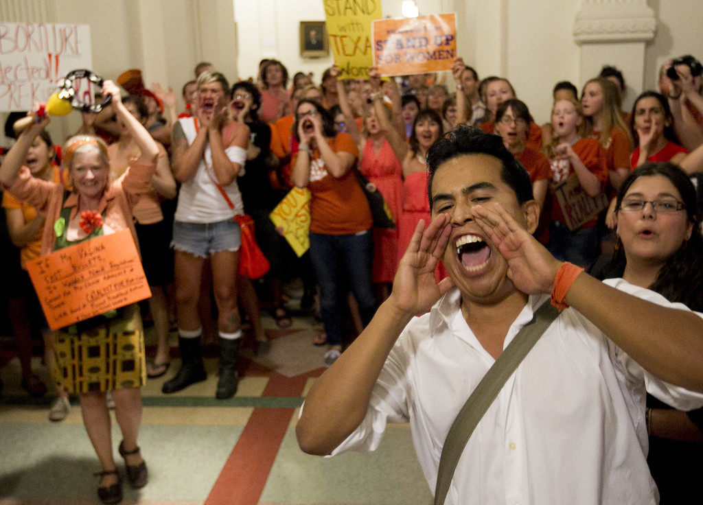 . Dave Cortez, right, and other abortion rights advocates scream outside the Senate Chamber during the debate of abortion restriction bill, Friday July 12, 2013, in the Capitol in Austin, Texas. Texas Republicans on Friday defended a sweeping abortion proposal against Democratic attempts to show the tough restrictions were not only unnecessary, but also unconstitutional. (AP Photo/Austin American-Statesman, Jay Janner)