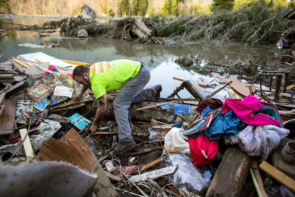 . Iraq War veteran and local Little League coach Matt Pater, 32, searches through debris following Saturday\'s destructive mudslide, near Oso Wash, Monday, March 24, 2014.  (AP Photo/seattlepi.com, Joshua Trujillo)