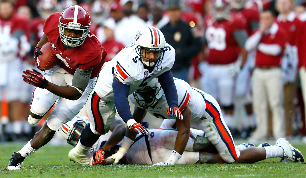 . Amari Cooper #9 of the Alabama Crimson Tide breaks a tackle by Jake Holland #5, Jermaine Whitehead #9 and Jonathon Mincy #6 of the Auburn Tigers on the way to a touchdown at Bryant-Denny Stadium on November 24, 2012 in Tuscaloosa, Alabama.  (Photo by Kevin C. Cox/Getty Images)