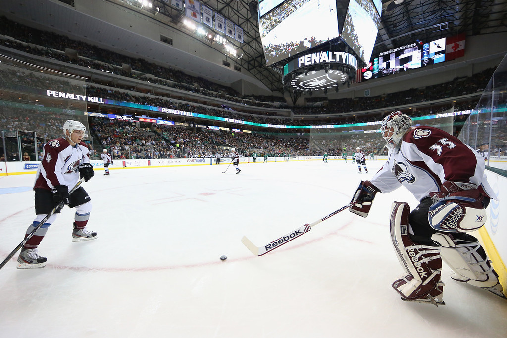. Jean-Sebastien Giguere #35 of the Colorado Avalanche plays the puck to Tyson Barrie #4 against the Dallas Stars in the first period at American Airlines Center on December 17, 2013 in Dallas, Texas.  (Photo by Ronald Martinez/Getty Images)