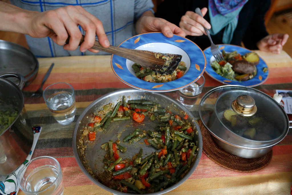 . Raphael Fellmer, a supporter of the foodsharing movement has lunch with his partner Nieves Palmer Muntaner, with food cooked from wasted vegetables from an organic supermarket in Berlin, January 24, 2013. Foodsharing is a German internet based platform where individuals, retailers or producers have the possibility of offering surplus food to consumers for free. Picture taken January 24.  REUTERS/Fabrizio Bensch