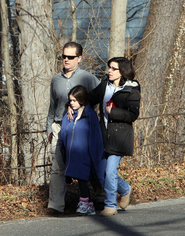 . Parents walk away from the Sandy Hook School with their children following a shooting at the school Friday, Dec. 14, 2012.  A man opened fire inside the Connecticut elementary school where his mother worked Friday, killing 26 people, including 18 children, and forcing students to cower in classrooms and then flee with the help of teachers and police. (AP Photo/The Journal News, Frank Becerra Jr.)