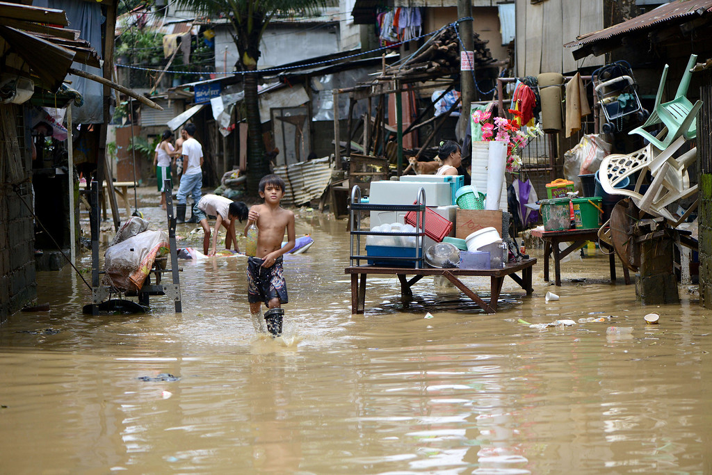 . A boy wades through a flooded street with furniture sitting out to dry as the residents clean the mud off their houses in San Mateo, Rizal, east of Manila on August 22, 2013.  Disaster-weary Philippine residents mopped up on August 22 after four days of torrential rain that officials said had killed 17 people and forced more than half a million from flooded homes. NOEL CELIS/AFP/Getty Images