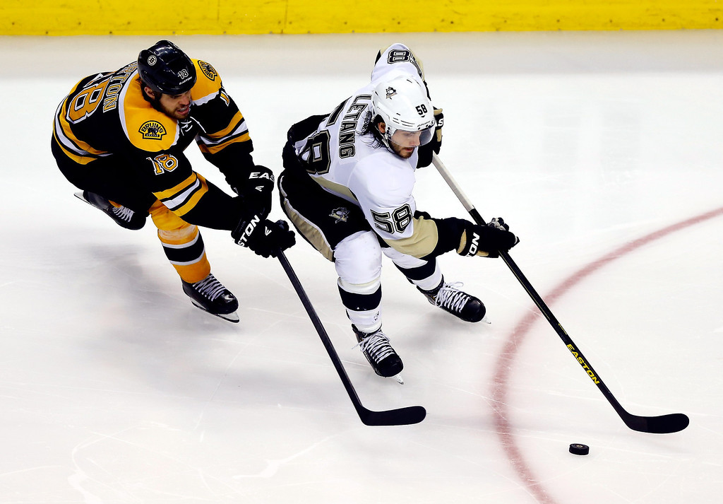 . Kris Letang #58 of the Pittsburgh Penguins skates with the puck as Nathan Horton #18 of the Boston Bruins defends during Game Three of the Eastern Conference Final of the 2013 NHL Stanley Cup Playoffs at the TD Garden on June 5, 2013 in Boston, Massachusetts.  (Photo by Jared Wickerham/Getty Images)
