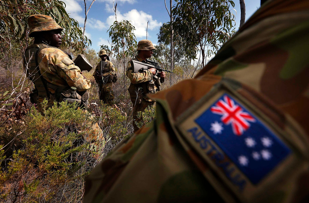 . Indigenous soldiers from Australia\'s North West Mobile Force (NORFORCE) unit, walk through thick bushland during a surveillance and reconnaissance patrol around Astell Island, part of the English Company Islands, located inside Arnhem Land in the Northern Territory July 17, 2013. NORFORCE is a surveillance unit that employs ancient Aboriginal skills to help in the seemingly impossible task of patrolling the country\'s vast northwest coast. NORFORCE\'s area of operations is about 1.8 million square km (700,000 square miles), covering the Northern Territory and the north of Western Australia. Aboriginal reservists make up a large proportion of the 600-strong unit, and bring to bear their knowledge of the land and the food it can provide. Fish, shellfish, turtle eggs and even insects supplement rations during the patrol, which is on the lookout for illegal foreign fishing vessels and drug smugglers, as well as people smugglers from neighboring Indonesia. Picture taken July 17, 2013. REUTERS/David Gray