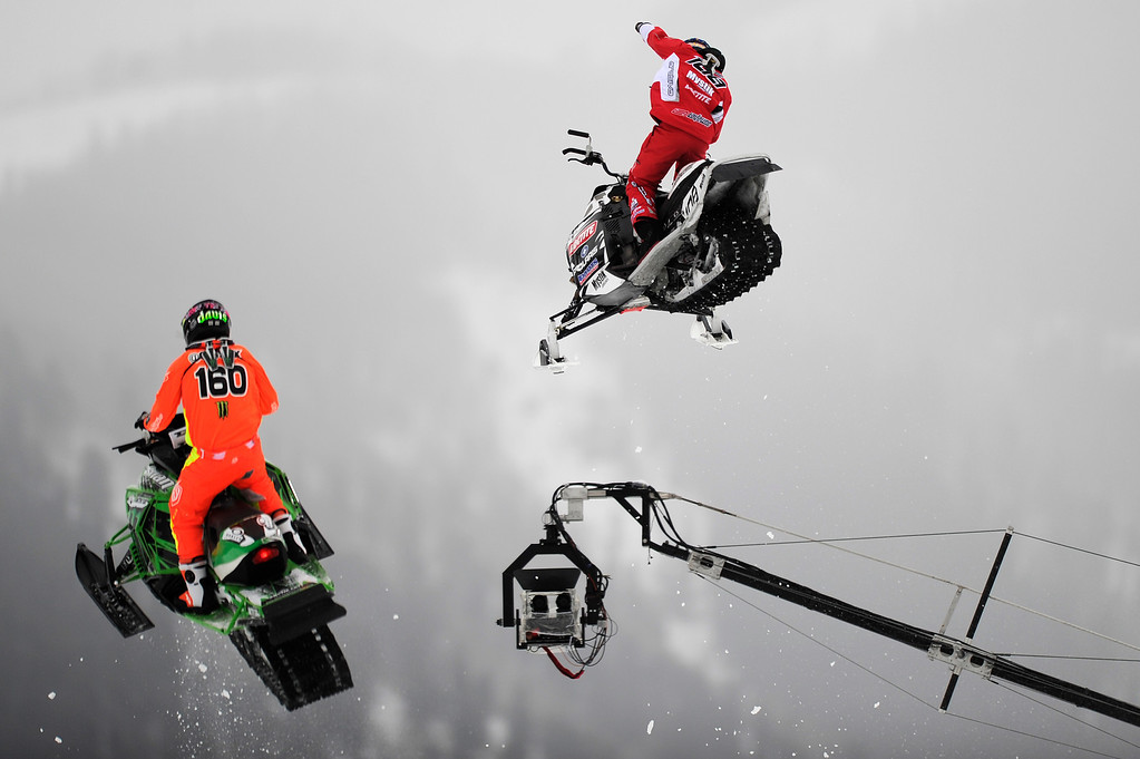 . ASPEN, CO - January 26: Levi LaVallee, right, raises his hand in victory while going over the final jump with Cory Davis, left, during the Snowmobile Speed & Style event at Winter X Games Aspen 2013 at Buttermilk Mountain on Jan. 26, 2013, in Aspen, Colorado. LaVallee won gold and Davis won silver in the event. (Photo by Daniel Petty/The Denver Post)