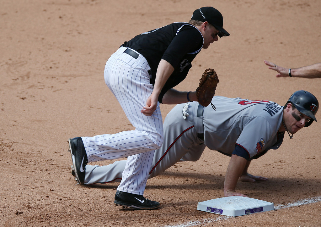 . Colorado Rockies first baseman Justin Morneau, front, turns to tag Minnesota Twins\' Josh Willingham who dives back into first base after a pickoff attempt  in the fifth inning of an interleague baseball game in Denver on Sunday, July 13, 2014. (AP Photo/David Zalubowski)