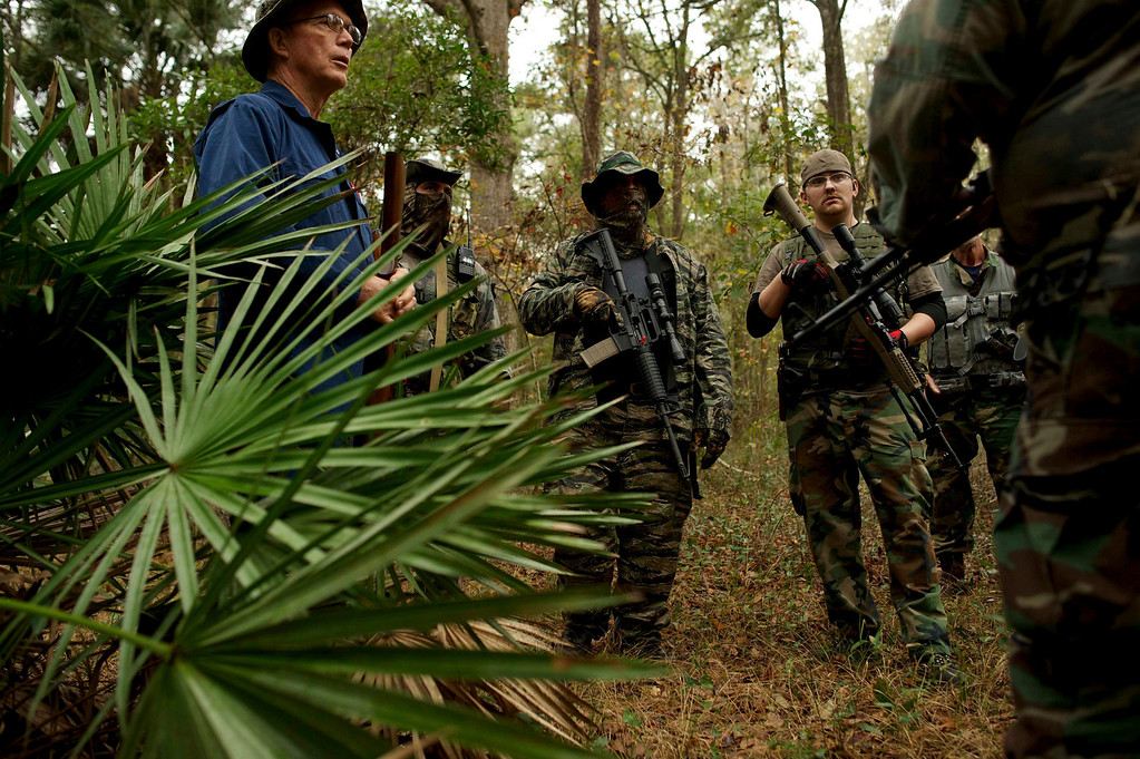 ". Members of the North Florida Survival Group listen as their leader critiques their performance during an enemy contact drill training exercise in Old Town, Florida, December 8, 2012.The group trains children and adults alike to handle weapons and survive in the wild. The group passionately supports the right of U.S. citizens to bear arms and its website states that it aims to teach ""patriots to survive in order to protect and defend our Constitution against all enemy threats\"". Picture taken December 8, 2013.   REUTERS/Brian Blanco"