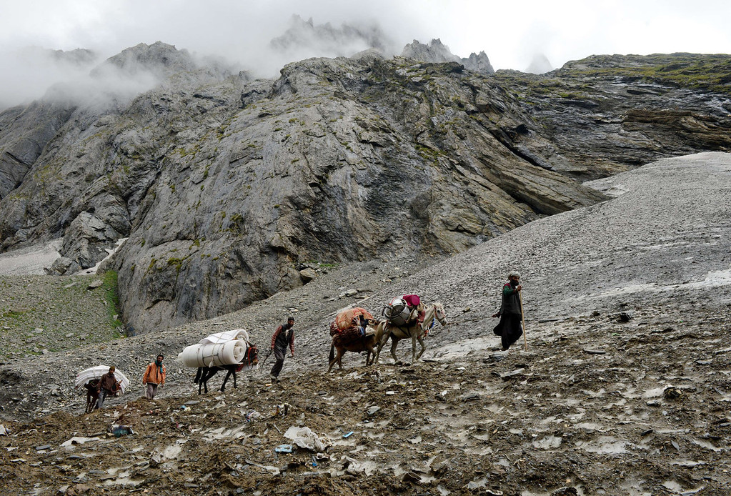 . Kashmiri muslims walk with horses on a glacier near Amarnath Cave on August 18, 2013. Every year, hundreds of thousands of pilgrims trek through treacherous mountains in revolt-torn Kashmir, along icy streams, glacier-fed lakes and frozen passes, to reach the Amarnath cave, located at an altitude of 3,857 meters (12,729 feet), where a Shiva Lingam, an ice stalagmite shaped as a phallus and symbolizing the Hindu God Shiva, stands for worship.   TAUSEEF MUSTAFA/AFP/Getty Images