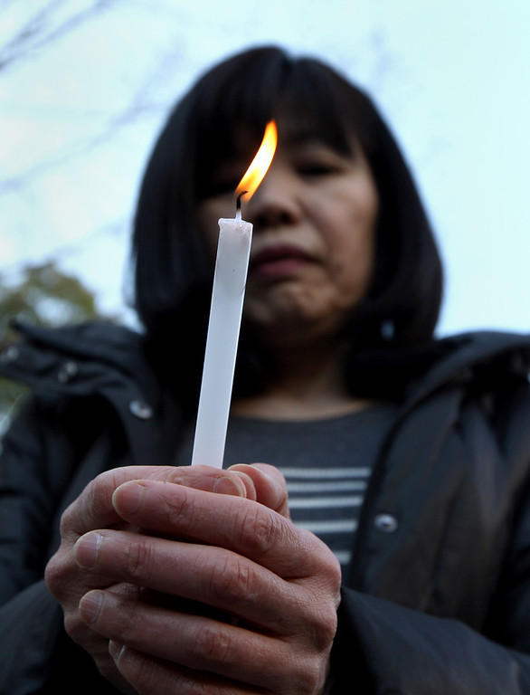 . A woman holds a candle as she commemorates victims of Great East Japan Earthquake and Tsunami in front of Kobe\'s light of hope memorial on March 11, 2013 in Kobe, Japan. Japan is commemorating the second anniversary of the 2011 Magnitude 9.0 earthquake and subsequent tsunami that claimed more than 18,000 lives.  (Photo by Buddhika Weerasinghe/Getty Images)