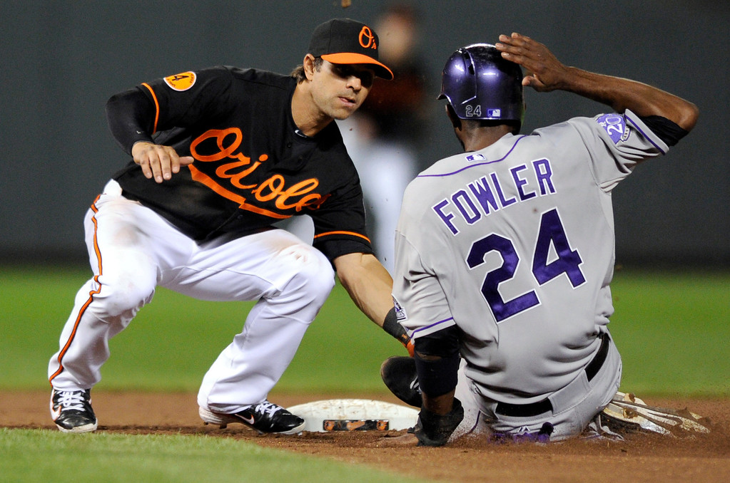 . Colorado Rockies\' Dexter Fowler (24) is tagged out by Baltimore Orioles second baseman Brian Roberts (1) as he tried to steal second during the eighth inning of a baseball game, Friday, Aug. 16, 2013, in Baltimore. The Rockies won 6-3. (AP Photo/Nick Wass)