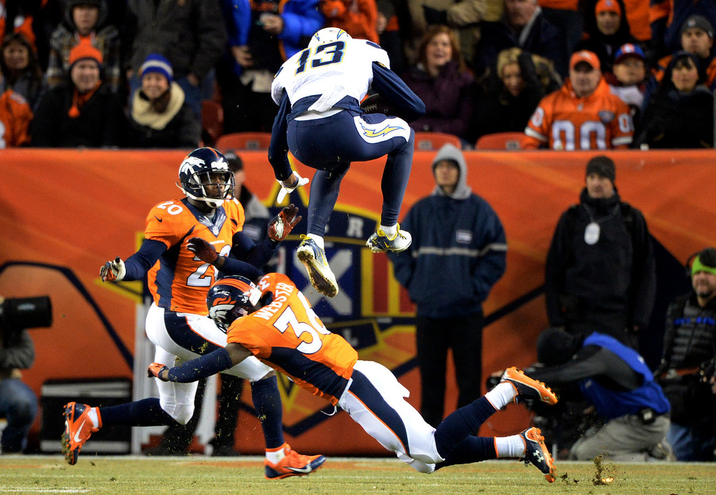 . San Diego Chargers wide receiver Keenan Allen (13) jumps over Denver Broncos cornerback Kayvon Webster (36) in the first half.  The Denver Broncos vs. the San Diego Chargers at Sports Authority Field at Mile High in Denver on December 12, 2013. (Photo by Hyoung Chang/The Denver Post)