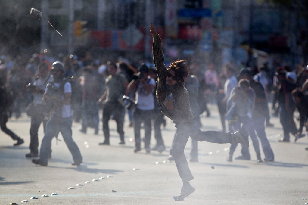 . A protestor throws a stone during clashes with police at a march commemorating the anniversary of the Tlatelolco massacre in Mexico City, Wednesday, Oct. 2, 2013. Mexico commemorated the 45th anniversary of the massacre of students holding an anti-government protest, killed by men with guns and soldiers in 1968 days before the Summer Olympics celebrations in Mexico City. (AP Photo/Eduardo Verdugo)