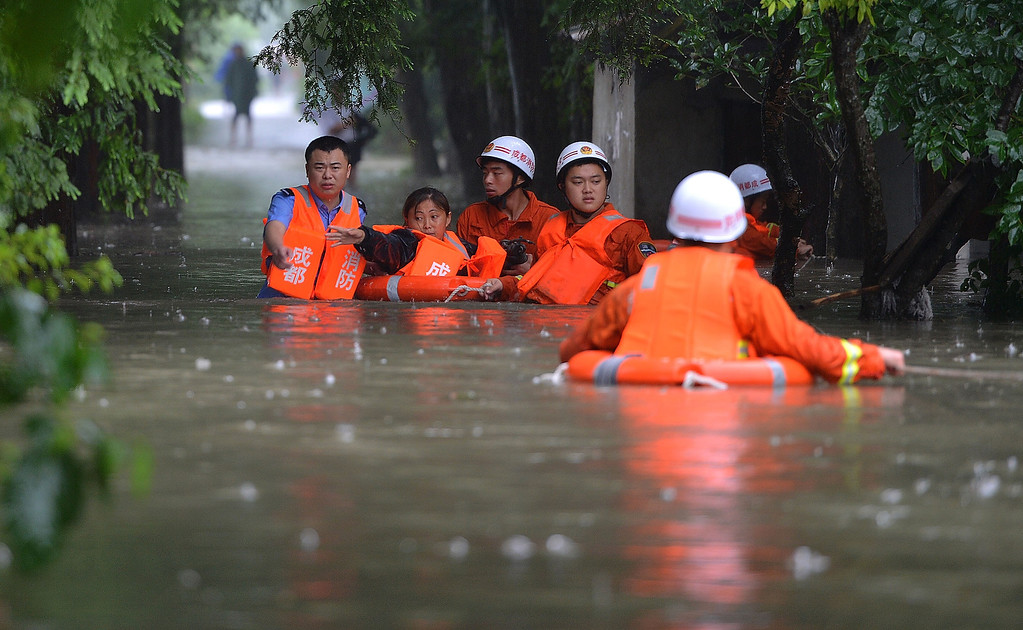 . Rescuers evacuate residents from flood-hit areas on July 9, 2013 in Chengdu, China. At least one person was killed and 15 others missing after severe rainstorms hit Sichuan province on Monday.  (Photo by ChinaFotoPress/ChinaFotoPress via Getty Images)