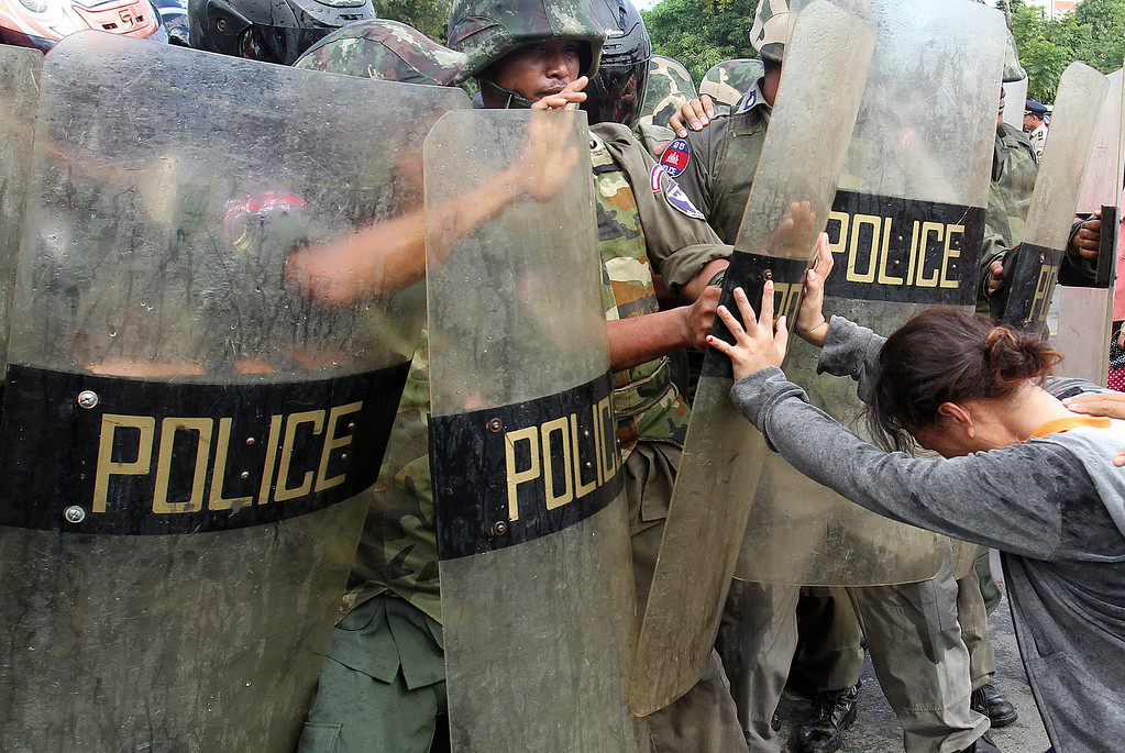. Riot police scuffle with residents of Boeung Kak lake during a protest in front of the City Hall in Phnom Penh November 28, 2011. Thousands of families living near the lake are facing eviction to make way for a Chinese development project. REUTERS/Samrang Pring