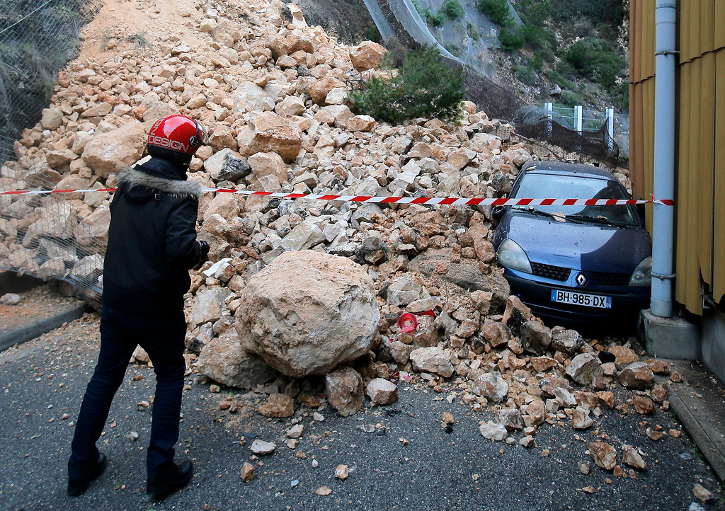 . A man looks at a parked car damaged outside a factory following a rockfall caused by heavy rain in La Londe Les Maures, near Toulon, southern France, Monday, Jan. 20, 2014. Unusually heavy rains have flooded the French Riviera, leaving two people dead and thousands without electricity or access to roads. (AP Photo/Lionel Cironneau)