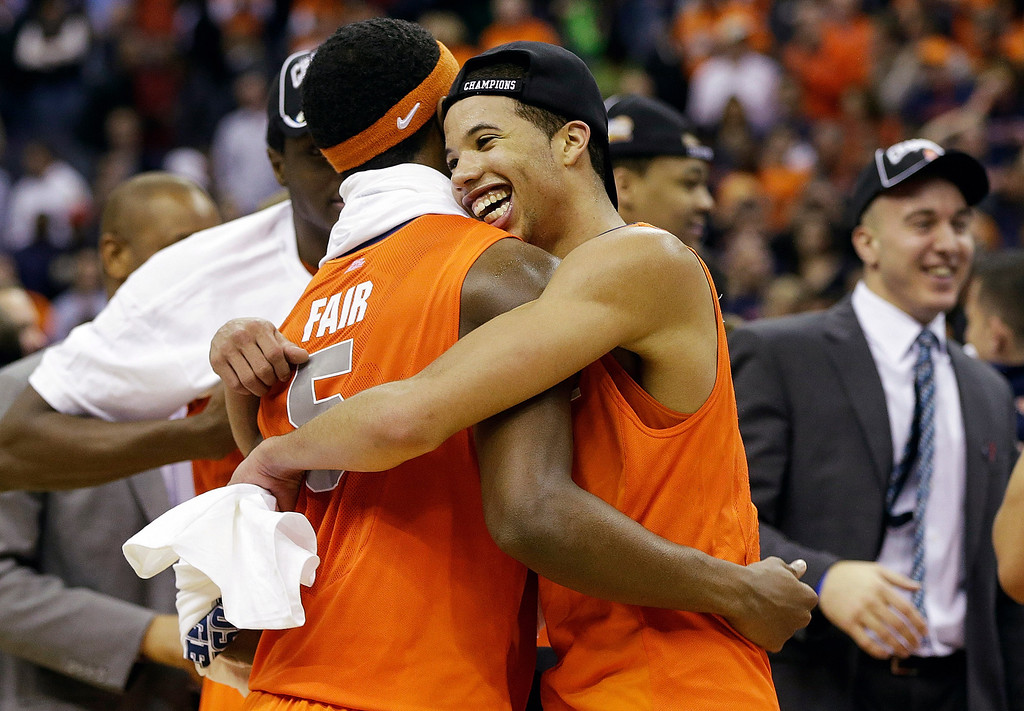 . Syracuse guard Michael Carter-Williams (1) hugs forward C.J. Fair (5) after their 55-39 win over Marquette in the East Regional final of the NCAA men\'s college basketball tournament, Saturday, March 30, 2013, in Washington. (AP Photo/Pablo Martinez Monsivais)