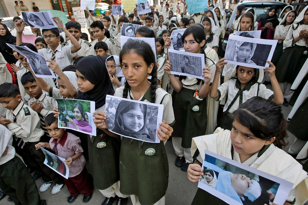 . Pakistani students hold pictures of 14-year-old schoolgirl Malala Yousufzai, who was shot last Tuesday by the Taliban for speaking out in support of education for women, during a protest condemning the attack, in Karachi, Pakistan, on Saturday, Oct. 13, 2012. (AP Photo/Fareed Khan)