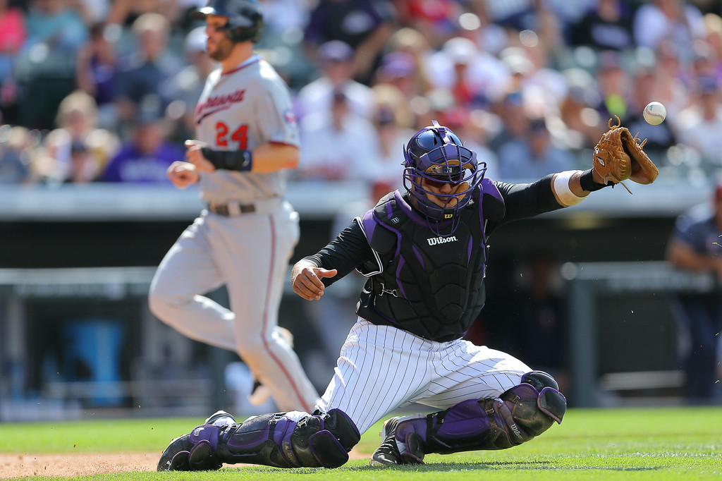 . Catcher Wilin Rosario #20 of the Colorado Rockies stops a wild throw from the outfield as Trevor Plouffe #24 of the Minnesota Twins strides in to score during the seventh inning at Coors Field on July 13, 2014 in Denver, Colorado. The Twins defeated the Rockies 13-5. (Photo by Justin Edmonds/Getty Images)