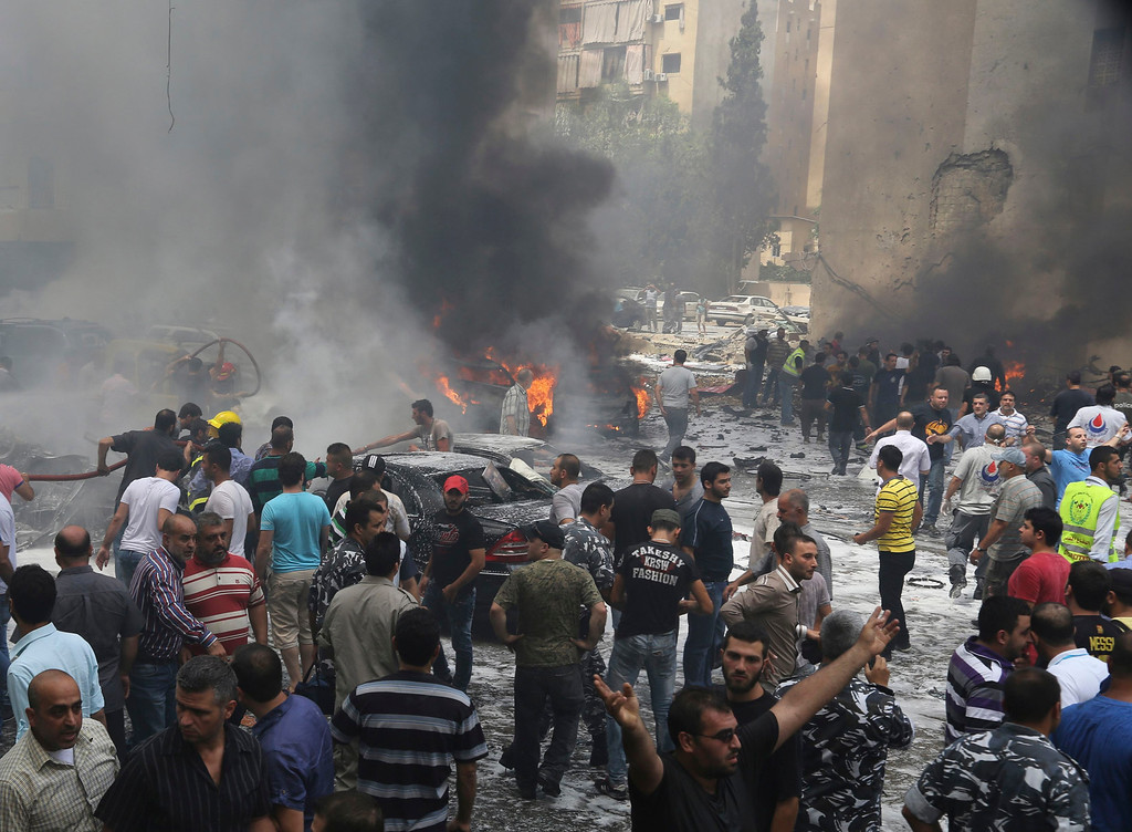 . Civil Defense workers, Hezbollah members, policemen and civilians gather at the site of an explosion in Beirut\'s southern suburbs, July 9, 2013.  REUTERS/Issam Kobeisi