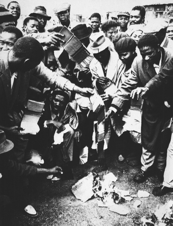 """. South African blacks burn government passes no longer required by them as new violence among the black population erupted at Orlando, near Johannesburg, South Africa, March 28, 1960. In violence centered around Johannesburg and Cape Town, police and Africans mixed when some blacks fought others of their race who insisted on going to work in defiance of a \""""Day of Mourning\"""" for those killed by white police just a week ago. (AP Photo/Dennis Lee Royle)"""