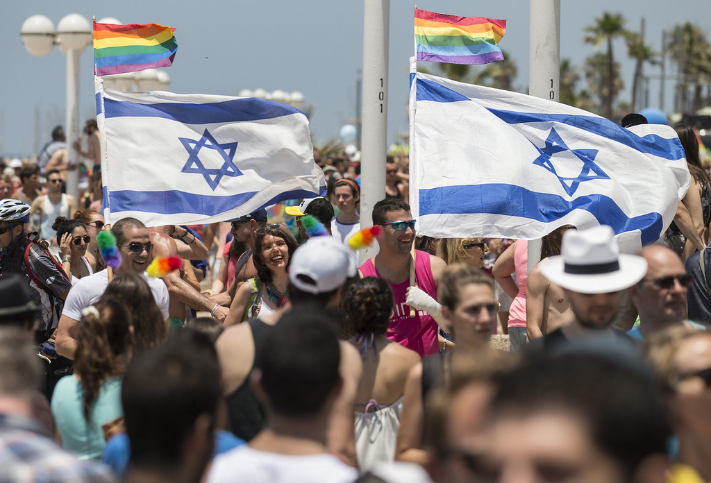 . Participants wave Israeli\'s flags during the annual gay pride parade in the Israeli coastal city of Tel Aviv on June 13, 2014. AFP PHOTO/JACK GUEZ/AFP/Getty Images