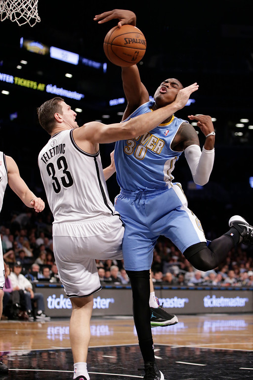 . Brooklyn Nets forward Mirza Teletovic (33) fouls Denver Nuggets forward Quincy Miller (30) in the second half of an NBA basketball game Tuesday, Dec. 3, 2013, in New York. (AP Photo/Kathy Willens)