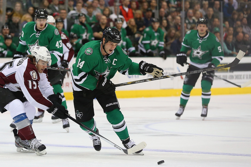 . Jamie Benn #14 of the Dallas Stars skates the puck against P.A. Parenteau #15 of the Colorado Avalanche in the first period at American Airlines Center on December 17, 2013 in Dallas, Texas.  (Photo by Ronald Martinez/Getty Images)