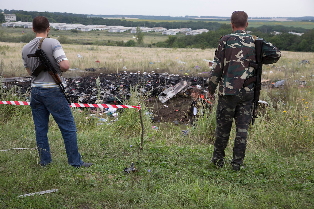 . Pro-Russian fighters guard the site of a crashed Malaysia Airlines passenger plane near the village of Rozsypne, Ukraine, eastern Ukraine Friday, July 18, 2014. Rescue workers, policemen and even off-duty coal miners were combing a sprawling area in eastern Ukraine near the Russian border where the Malaysian plane ended up in burning pieces Thursday, killing all 298 aboard. (AP Photo/Dmitry Lovetsky)
