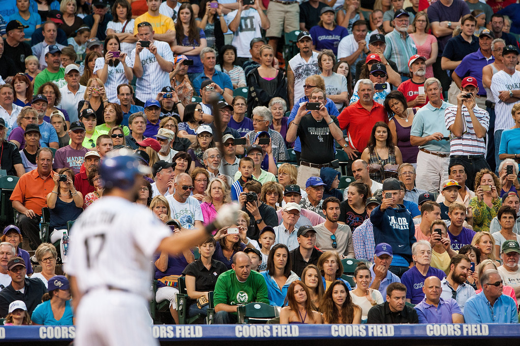. Fans point their cameras toward home plate as Todd Helton #17 of the Colorado Rockies attempts to reach 2,500 career hits in the second inning of a game against the Cincinnati Reds at Coors Field in August 2013. (Photo by Dustin Bradford/Getty Images)