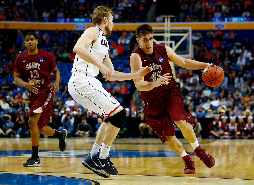 . BUFFALO, NY - MARCH 20: Halil Kanacevic #45 of the Saint Joseph\'s Hawks drives to the basket as Niels Giffey #5 of the Connecticut Huskies defends during the second round of the 2014 NCAA Men\'s Basketball Tournament at the First Niagara Center on March 20, 2014 in Buffalo, New York.  (Photo by Jared Wickerham/Getty Images)