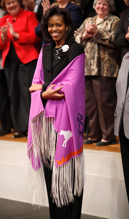 . In this Feb. 9, 2009 file photo, first Lady Michelle Obama models a handmade shawl she received from Director of Public Affairs for the Bureau of Indian Affairs Nedra Darling during an event at the Interior Department in Washington. (AP Photo/Lawrence Jackson, File)