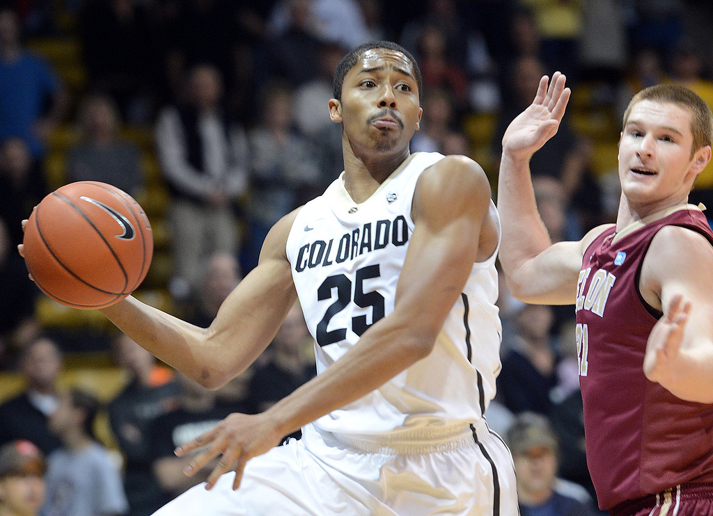 . Spencer Dinwiddie of CU passes around Ryley Beaumont of Elon during the first half of the December 13, 2013 game in Boulder. (Cliff Grassmick/Boulder Daily Camera)