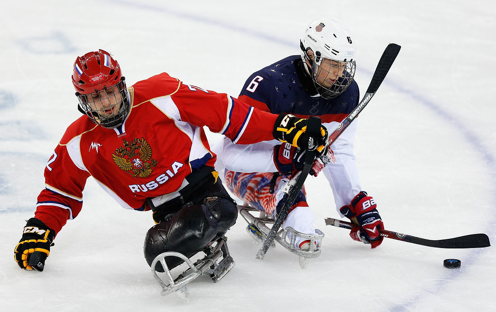 . Declan Farmer of USA (R) clashes with Nikolay Terentyev of Russia during the Ice Sledge Hockey Gold Medal match between Russia and USA at the Shayba Arena during day eight of the 2014 Paralympic Winter Games on March 15, 2014 in Sochi, Russia.  (Photo by Harry Engels/Getty Images)
