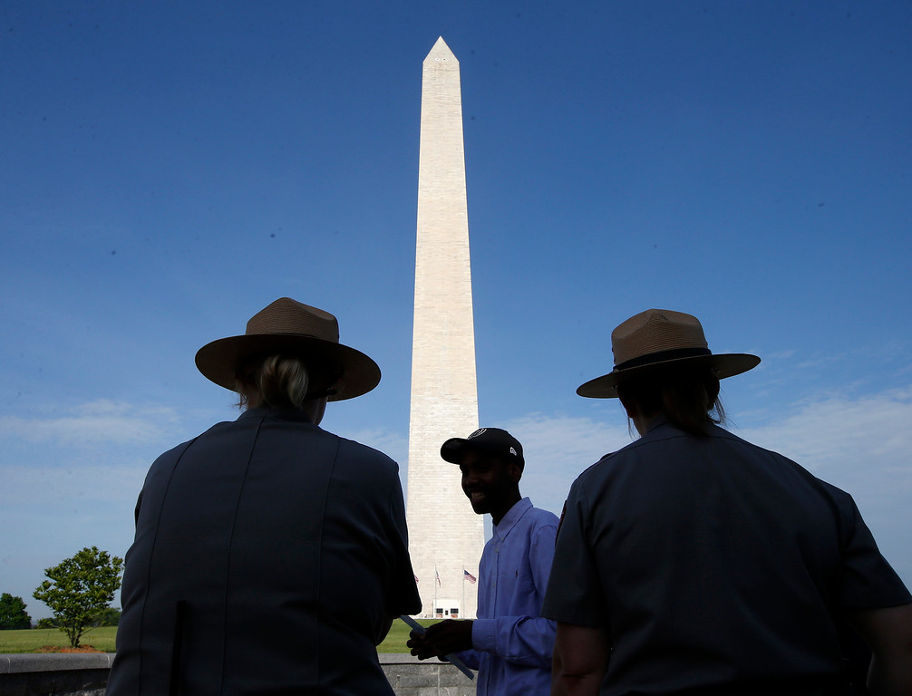 . Park Service employees stand watch as visitor Roman Tanner, center, walks away with his Washington Monument ticket, which are distributed at on a first-come basis at the Washington Monument in Washington, Monday, May 12, 2014, ahead of a ceremony to celebrate its re-opening.  (AP Photo)