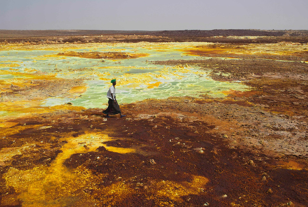 . A man walks on sulphur and mineral salt formations near Dallol in the Danakil Depression, northern Ethiopia April 22, 2013. The Danakil Depression in Ethiopia is one of the hottest and harshest environments on earth, with an average annual temperature of 94 degrees Fahrenheit (34.4 Celsius). For centuries, merchants have travelled there with caravans of camels to collect salt from the surface of the vast desert basin. The mineral is extracted and shaped into slabs, then loaded onto the animals before being transported back across the desert so that it can be sold around the country. Picture taken April 22, 2013. REUTERS/Siegfried Modola