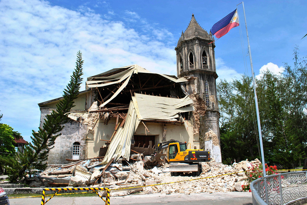 . A crane shifts through the rubble of the damaged Our Lady of Assumption Parish church following a 7.2-magnitude earthquake, at Dauis in Bohol, central Philippines, Tuesday Oct. 15, 2013. (AP Photo)