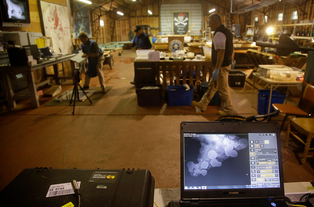 . An X-ray of a concretion, front,  a rocky mass that forms when metals such as gold and silver chemically react to salt water, is seen on a laptop computer at the Whydah pirate ship museum\'s warehouse in Brewster, Mass., Tuesday, Sept. 17, 2013. Undersea explorer Barry Clifford and his team took the season\'s final trip to the Whydah, the only authenticated pirate ship wreck in U.S. waters.  (AP Photo/Stephan Savoia)
