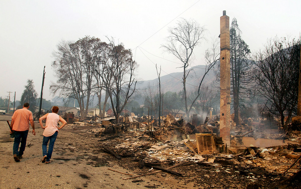 . A couple walks near a burned out home in Pateros Wash., on Friday, July 18, 2014. Authorities say the wildfire has already burned about 100 homes and prompted the evacuation of Pateros, home to about 650 people in Okanogan County. A hospital in nearby Brewster was also evacuated as a precaution.  (AP Photo/The Wenatchee World, Mike Bonnicksen)