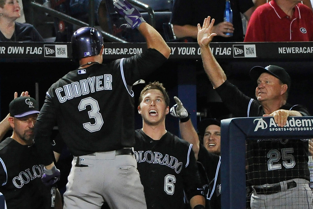 . Colorado Rockies\' Michael Cuddyer (3) is greeted by Corey Dickerson (6) and hitting coach Blake Doyle (25) after Cuddyear\'s solo home run against the Atlanta Braves during the sixth inning of a baseball game Friday, May 23, 2014, in Atlanta. (AP Photo/David Tulis)
