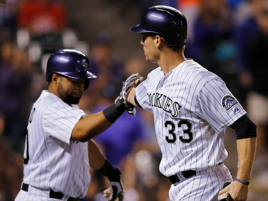 . Colorado Rockies\' Justin Morneau (33) is congratulated by Wilin Rosario after scoring a run against the Cincinnati Reds during the sixth inning of a baseball game Friday, Aug. 15, 2014, in Denver. (AP Photo/Jack Dempsey)