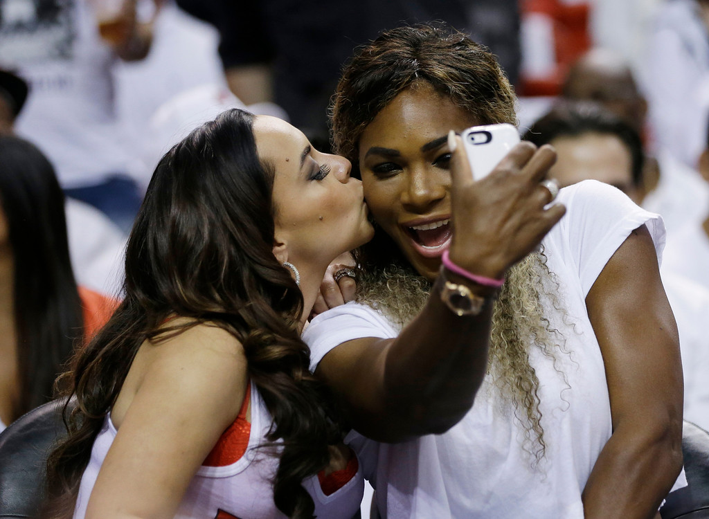 . Adrienne Bosh, left, wife of Miami Heat player Chris Bosh, kisses tennis player Serena Williams as Willians takes a photo during the first half Game 6 in the NBA basketball playoffs Eastern Conference finals between the Indiana Pacers and the Heat, Friday, May 30, 2014, in Miami. (AP Photo/Lynne Sladky)