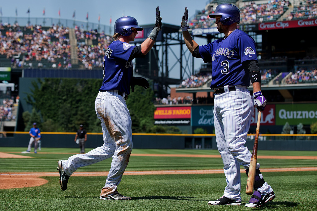 . Charlie Blackmon #19 and Michael Cuddyer #3 of the Colorado Rockies celebrate after scoring during the first inning against the Chicago Cubs at Coors Field on July 21, 2013 in Denver, Colorado.  (Photo by Justin Edmonds/Getty Images)