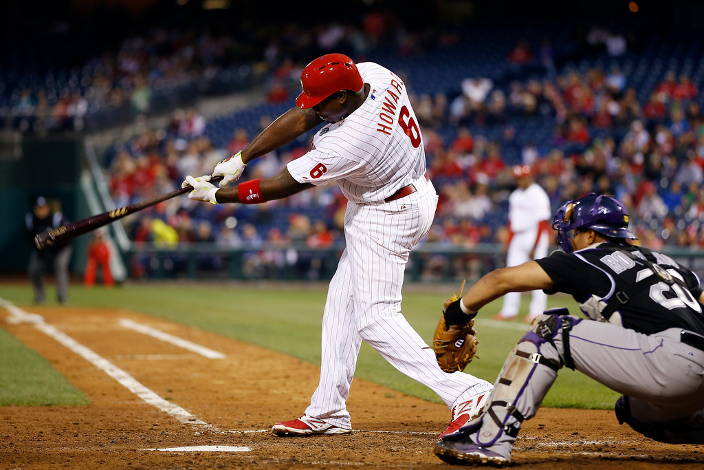 . Philadelphia Phillies\' Ryan Howard follows through after hitting an RBI single off Colorado Rockies starting pitcher Jordan Lyles during the third inning of a baseball game, Wednesday, May 28, 2014, in Philadelphia. At right is catcher Wilin Rosario. (AP Photo/Matt Slocum)