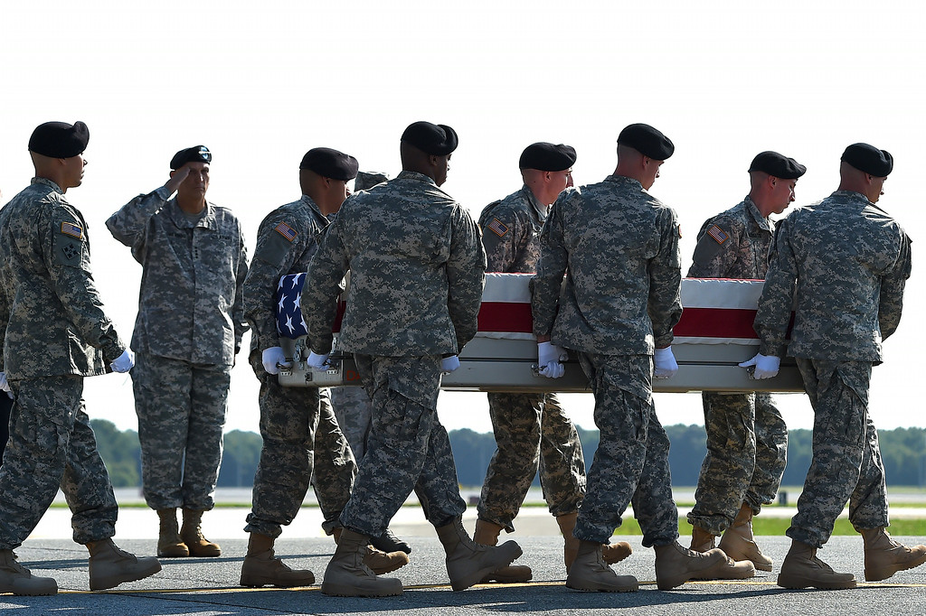 . U.S. Army soldiers carry the flag-draped transfer case containing the remains of U.S. Army Maj. Gen. Harold J. Greene during a dignified transfer, as U.S. Army Chief of Staff Ray Odierno salutes, at Dover Air Force Base on August 7, 2014 in Dover, Delaware.  (Photo by Patrick Smith/Getty Images)