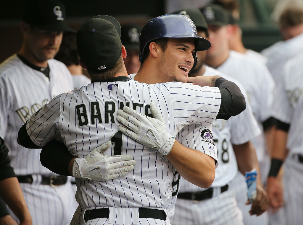 . DENVER, CO - AUGUST 15:  Nolan Arenado #28 of the Colorado Rockies celebrates his solo home run off of Johnny Cueto #47 of the Cincinnati Reds with Brandon Barnes #1 of the Colorado Rockies to give the Rockies a 1-0 lead in the second inning at Coors Field on August 15, 2014 in Denver, Colorado.  (Photo by Doug Pensinger/Getty Images)