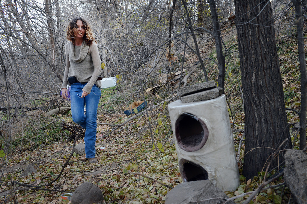 . Kelly Uhing, of the Denver Department of Parks and Recreation, examines shelters left for a colony of feral cats along South Platte River Dr. in Denver, CO, Thursday December 06, 2012.  Craig F. Walker, The Denver Post