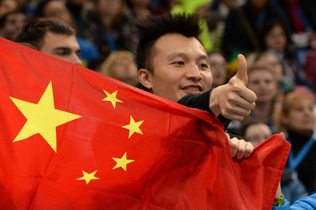 . A Chinese fan holds China\'s flag and gives a thumb up during the Men\'s Figure Skating Short Program at the Iceberg Skating Palace during the Sochi Winter Olympics on February 13, 2014.   YURI KADOBNOV/AFP/Getty Images